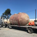 Large storage tank strapped to trailer bed