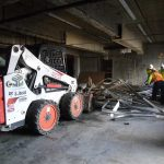 Workers using Bobcat to remove metal material from construction site after demolition