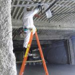 Demolition worker removing fireproofing material from ceiling